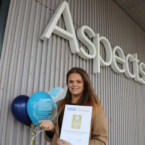 Aspects Team Member holding the Gold Award and Balloons